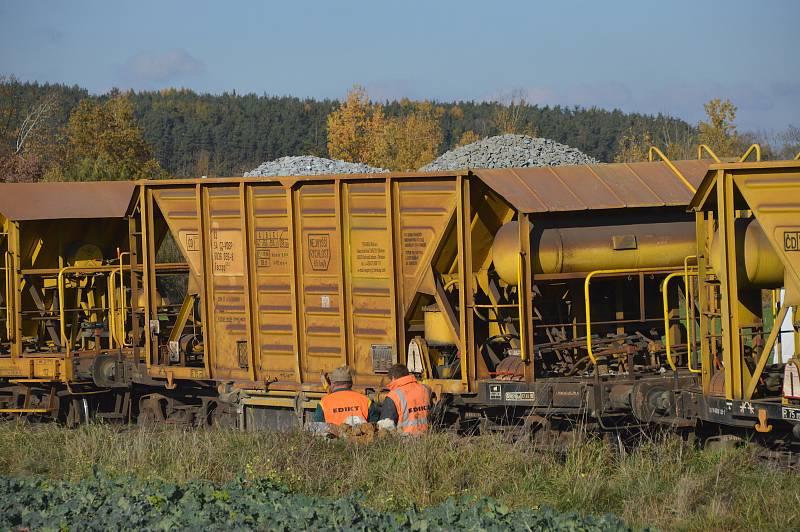 Dělníci firmy ovládají nákladní vůz pro sypání štěrku.