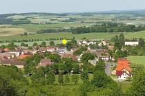 Újezd z Hrádku. Obec by se mohla podle územního plánu rozšířit do prostoru (dnes pole), který jsme označili žlutě. Vpravo v popředí nové domy, ale v této části Újezda je stavební uzávěra.