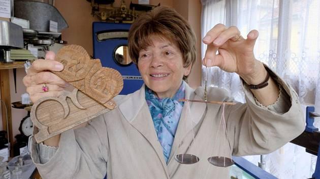Průvodkyně Věra Mariánová ukazuje malé kapesní váhy na opium a dřevěné pouzdro s vyřezávanými slony, do kterého se ukrývají. Exponát pochází z Barmy.