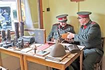 Četník Petr Mareš nabízí svému kolegovi Radkovi Tomanovi cigaretu. V chatce na koupališti Podhájí se krátkodobě usídlila četnická stanice jako vystřižená z dob první republiky.
