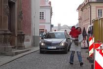 SILNICE SLOUŽÍ JAKO CHODNÍK. Lidé před kostelem procházejí po silnici, kde se vyhýbají autům.