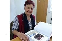 Zdeňka Starinská s kronikou, do níž vlepuje články, fotografie a zaznamenává dění v obci.