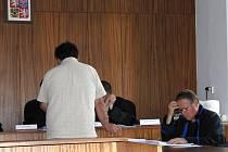 Ze soudní síně. Obžalovaný prohlíží fotodokumentaci ze spisu.