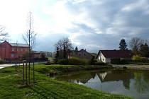 Kramolínská náves se zvoničkou, parčíkem a rybníčkem. Zcela vlevo budova obecního úřadu, kde sídlí i mateřská škola.