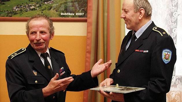 Zástupce okresního sdružení Václav Ponocný předává ocenění odstupujícímu      veliteli okrsku č. 10 Jiřímu Štauberovi. Tuto funkci vykonával úctyhodných 27 let.