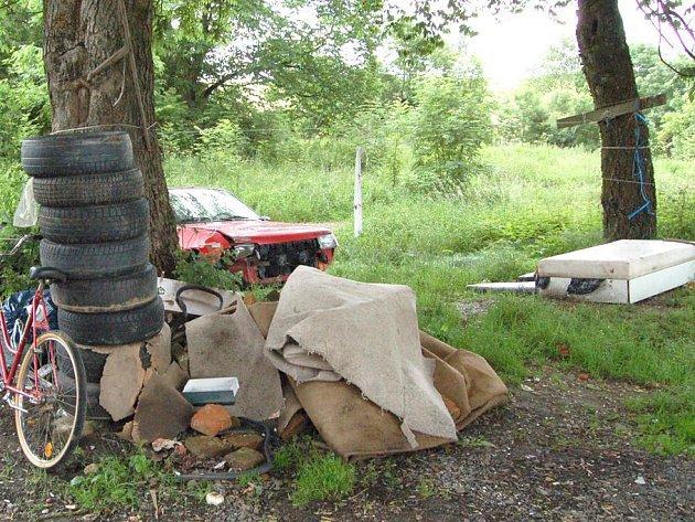 Vrak auta, pneumatiky, starou postel a jiné klenoty na obecním pozemku Danielovi  za nepořádek nepovažují.