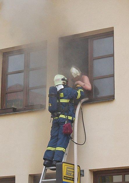 Hasič pomáhá jednomu z obyvatel z hořícího domu