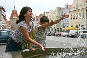 """Děti se osvěžují u kašny na domažlickém náměstí. """"Chladivá voda z kašny je cítit na metry daleko. Přináší myšlenky na den strávený u koupaliště,"""" říká Jan Rausková z Domažlic."""
