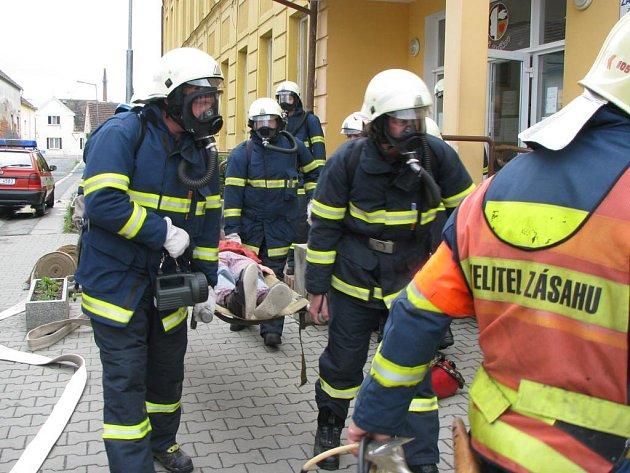 Při prověřovacím cvičení vynášeli hasiči několik žáků na nosítkách.