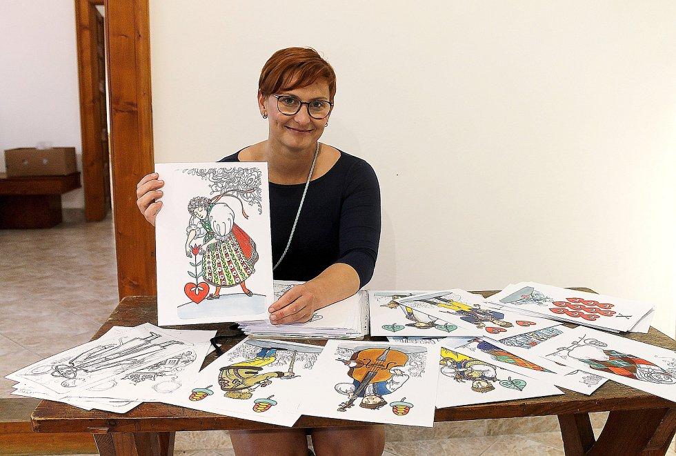 Kurátorka výstavy a historička Kristýna Pinkrová ukazuje kresby chodského mariáše od Slávky Štrbové.