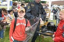 Při včerejším Dni z Integrovaným záchranným systémem v Domažlicích kluky nejvíce zajímala policejní výzbroj a výstroj. Ti malí pak soutěžili u stolků (v pozadí), kde se jim věnovaly ženy – policistky.