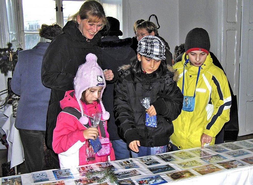 Sbírku vánočních pohlednic Anny Prantlové si na snímku se zájmem prohlížejí (vpředu zleva) Eliška Tušková, Tereza Hrušková a Daniel Melich z Klenčí pod Čerchovem, spolu s nimi se dívá i trhanovská zastupitelka Marie Novotná.