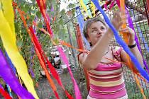 Marie Ticháčková věší barevné pentle na mladou břízku.