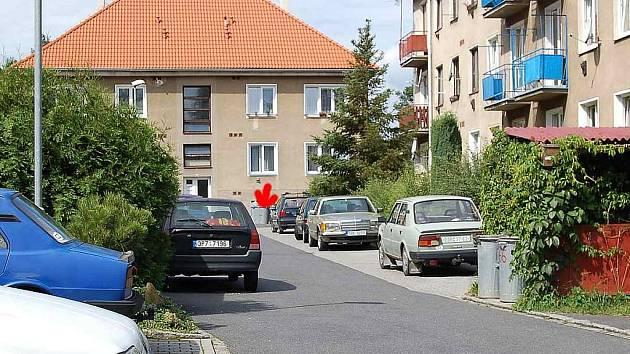 Kvůli bezohledně parkujícím autům zůstaly nevyvezené popelnice (viz červená šipka) pro tři bytové domy.