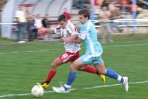 TAKHLE MUSÍME I NA DOUBRAVKU! Holýšovský Petr Jeniš prchá horažďovickému hráči v posledním domácím zápase.