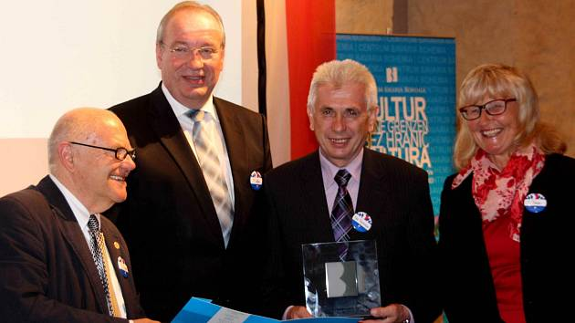 KARL REITMEIER (druhý zprava) byl dojatý, když přebíral ocenění, jež mu v Centru Bavaria Bohemia v Schönsee předali (zleva) ředitel CeBB Hans Eibauer, chamský zemský rada Franz Löffler a Irene Träxler, předsedkyně obecně prospěšného spolku Bavaria Bohemia