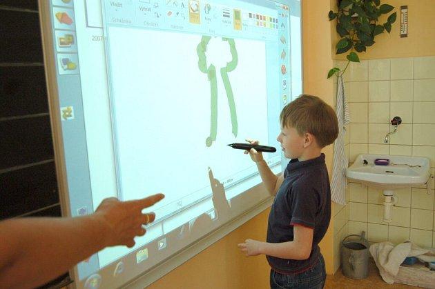 Žák domažlické školy kreslí speciální tužkou na interaktivní tabuli.