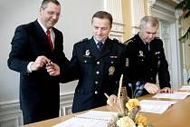 Domažlický starosta Miroslav Mach půjčuje pero vedoucímu Územního odboru vnější služby v Domažlicích Miloslavu Horovi. Spolu s krajským policejním ředitelem Miloslavem Mašterou (v pozadí) podepsali koordinační dohodu v obřadní síni Městského úřadu.