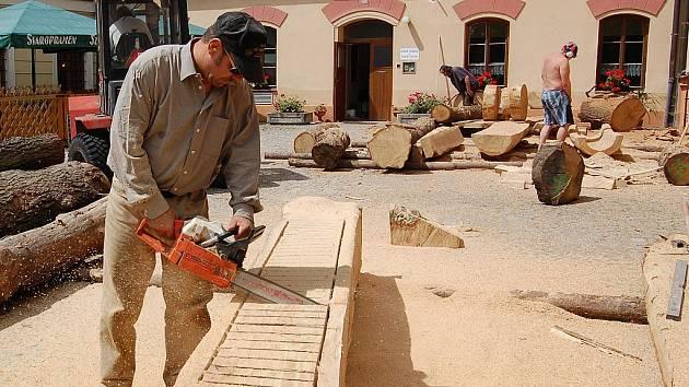 zatímco před Chopdským hradem už od pondělka vznikají dřevěné sochy, pod ním bude ode dneška hudební festival. Na snímku na svém díle pracuje Rakušan Herman Gschaider