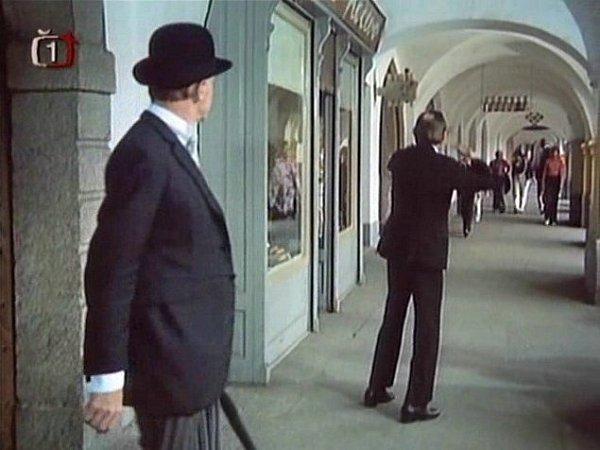 Vystrašený děda Hanousek (J. Kemr, vpravo) vyběhl v63. minutě filmu zbytu, když uviděl Pana Tau, kterému chyběla spodní část těla. Na místě je dnes Chodská pekárna. Vpozadí vidíme nápis Lékárna vytvořený na láhvích, který se od 70.let nezměnil.