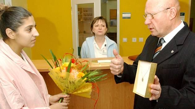 Primátor Divíšek předává matce prvního hradeckého občánka upomínkové předměty.