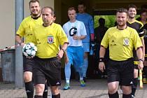 Jde se na věc... Trojice rozhodčích v čele s hlavním Otakarem Pešavou (s míčem) přivádí dva týmy na hrací plochu, kde se o chvíli později rozběhne jedno z mistrovských utkání.
