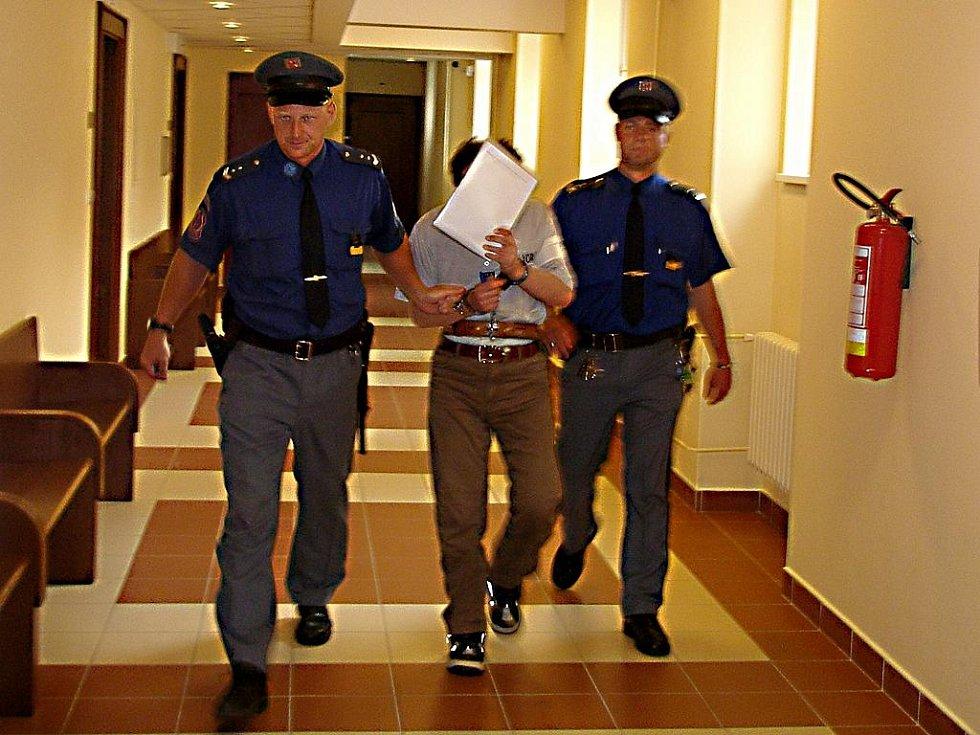 Soud vyhověl přání obžalovaného Jiřího Homoly a nepovolil fotografofání v jednací síni. I v eskortě se Homola ukrýval.