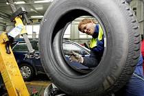 """Pracovníci pneuservisu při """"přezouvání"""" automobilu."""