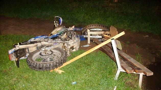 Havarovaný motocykl a poničená lavička.