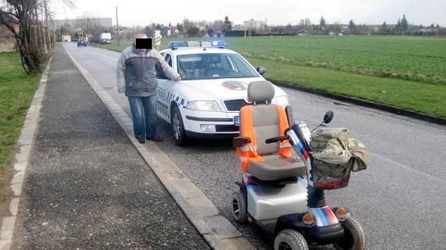 Pomoc muži na elektrickém invalidním vozíku.
