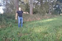 Němčický starosta Jaroslav Štěpánek ukazuje na úzký pruh půdy, která brání výstavbě lávky na cyklostezce z Hradce Králové do Pardubic.