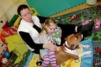 Dítě v hradecké MŠ Slunečnice při canisterapii - léčebném kontaktu se psem.