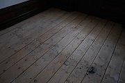 Podlaha v hostinksém pokoji před opravou.