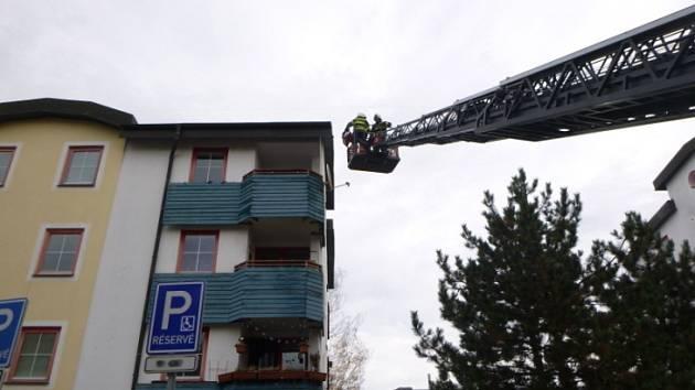 Náraz větru uvolnil plechovou krytinu na střeše panelového domu.