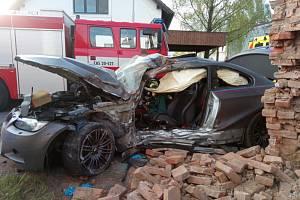 Muž naboural do domu a zůstal zaklíněný v autě.
