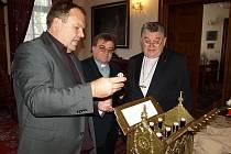 Nasik Kiriakovský představil pražskému arcibiskupovi Mons. Dominiku Dukovi pivo Tambor, které bylo určeno jako speciální dar pro papežský stolec. Sládek Martin Vrba je zachycen při své práci v pivovaru.