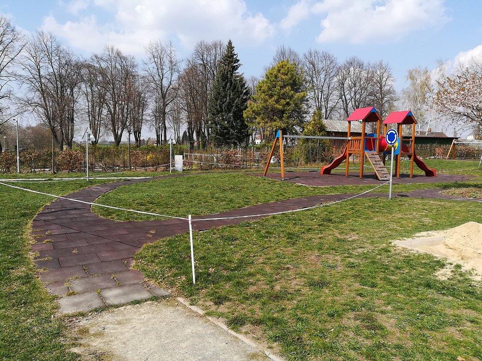 Poničené tartanové dlaždice jsou pod většinou atrakcí na dětském hřišti.