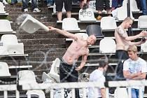 Příznivec ostravského Baníku na hradeckém fotbalovém stadionu s utrženou plastovou sedačkou v ruce.