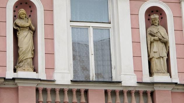 Dvě sochy na domě v hradecké Komenského ulici