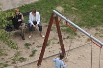 """Všední obrázek. Zatímco dítě si užívá na hřišti, dospělí opodál bez bázně a hany """"vykuřují""""."""