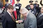 Prezident Miloš Zeman se vítá s hejtmanem Královéhradeckého kraje Lubomírem Francem a prohlíží si medaili na jeho krku.