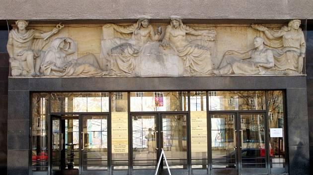 Reliéf s motivem cestování a železnice na stavbě na hradeckém Ulrichově náměstí.