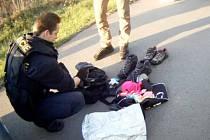 Strážník vybalující tašku plnou ukradeného zboží.