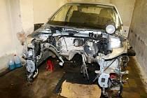Rozebraný automobil v garáži.