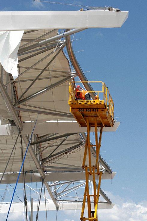 Na konstrukci v těchto dnech natahují pracovníci plachtu.