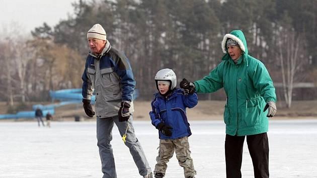 Zamrzlá hladina Stříbrného rybníku je vodou na mlýn pro vyznavače zimních radovánek.