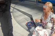 Žena bez domova žebrající peníze od kolemjdoucích.