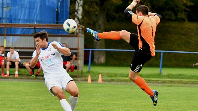 Kung-fu? Ne, to jen bydžovský gólman David Průcha odkopává míč před hráčem Kostelce.
