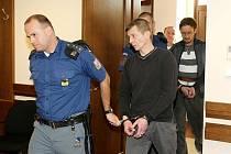 MOŽNÁ I DOŽIVOTÍ hrozí dvěma kumpánům, kteří se upálením čtyř lidí zaživa chtěli letos v únoru v českotřebovské místní části Lhotka zbavit nepohodlných sousedů. Na snímku je justiční stráž přivádí k hlavnímu líčení.