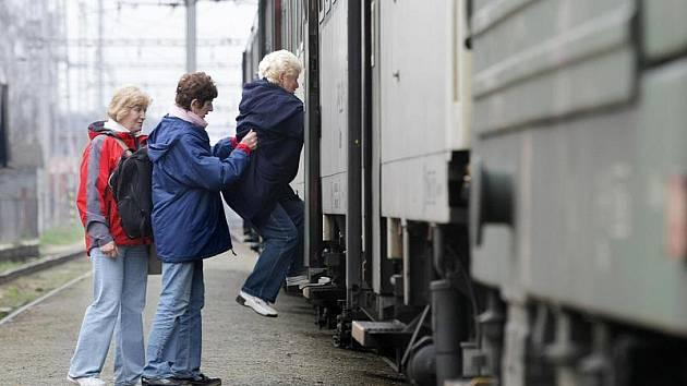 Vysoké vagony, ale nezvýšené nástupiště. Přátelská výpomoc při nástupu do vlaku, denní obrázek z týništského nádraží.